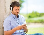 Young man using cell phone and head phones outside