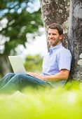 Young man working outside on laptop in park under a tree