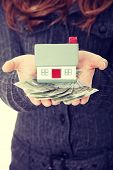 Young businesswoman holding euros bills and house model over white - real estate loan concept