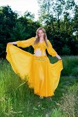 beautiful woman in yellow dress posing in nature