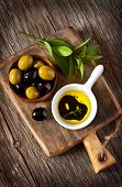 stock photo of vinegar  - Green and black olives and olive oil with balsamic vinegar on wooden cutting board - JPG