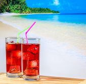 Two Glasses Of Red Cocktail With Blur Beach And Space For Text
