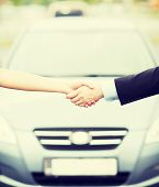 transportation, business, shopping and ownership concept - customer and salesman shaking hands outsi