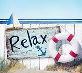 Wooden Fence and Relax Sign Board on Beach