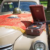 Car cowl GAZ-M-20 Pobeda with an old record player and a lying flag on show of collection Retrofest
