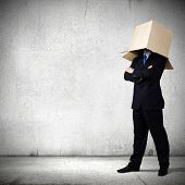 Businessman in suit wearing carton box on head