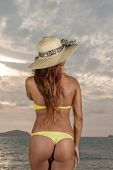 Thai girl with straw hat on the beach