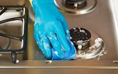 Hand Wearing Rubber Glove While Cleaning Stove Top Range With Soapy Sponge