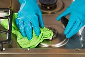 Gloved Hands Removing Soap From Stove Top Range With Microfiber Rag