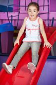 Scared girl sitting on a slide in a kindergarten