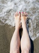 Woman Feet Relaxing On The Shore Waiting For  Wave