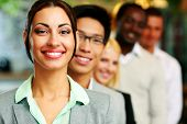 Smiling businesswoman standing in front of colleagues
