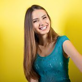 Joyful excited happy laughing young woman over yellow background.