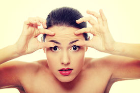 picture of forehead  - Woman checking her wrinkles on her forehead - JPG