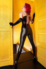 picture of latex woman  - Beautiful young woman in tight sexy outfit standing in doorway - JPG
