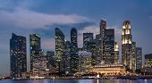 Singapore Business Tower At Night, Cityscape And Skyline Panorama At Dusk Over The Sea With Colorful