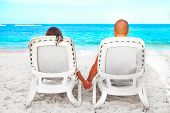 Couple Relaxing On Sunbed