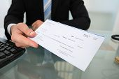 picture of receipt  - Midsection of businessman giving cheque at desk in office - JPG