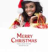 Festive woman standing looking while holding bags against merry christmas