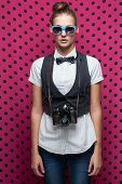 Portrait Of Beautiful Hipster Style Young Woman In White Shirt And Bow-tie. Old Camera Hanging By Th