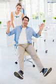 Man on swivel chair with hands up in office