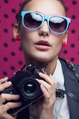 Close Up Of Fashionable Girl With Old Camera In Blue Sunglasses On Dotted Pink Background