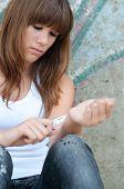 image of wrist  - Pretty depressed teenage girl preparing to cut her wrists open - JPG