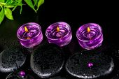 Spa Still Life Of Zen Basalt Stones With Beads, Drops, Lilac Candles And Green Bamboo, Closeup