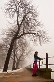Lonely teenage girl watching the mist on cold winter day