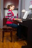 Pretty smiling teenage girl playing on piano in her room