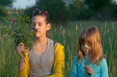 Two cute girls picking flowers on the meadow
