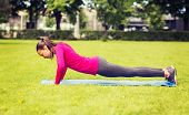 fitness, sport, training, park and lifestyle concept - smiling woman doing doing push-ups on mat outdoors