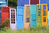 Collection of colorful old wooden doors leaning on fence