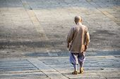 Buddhist monk walking down an incline.