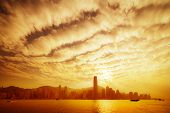 Hong Kong Skyline In Golden Dusk With Dramatic Clouds