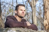 stock photo of stare  - Scruffy handsome Caucasian man with arms crossed leaning over fallen log in thick wooded area stares off into distance in deep thought - JPG