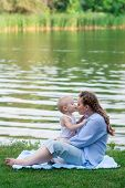 Motherhood. Boy kissing his pregnant mother outdoors