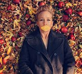 a woman in a nice jacket with a a leaf over her mouth laying in a pile of leaves and apples toned with a retro vintage instagram like filter effect