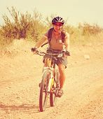 a girl riding a mountain bike in the hills toned with a retro vintage instagram filter effect