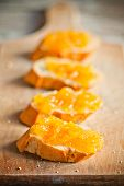 pieces of baguette with orange marmalade closeup wooden board