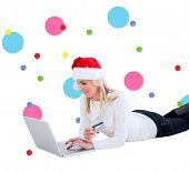 Festive blonde shopping online with laptop against dot pattern