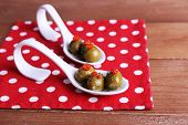 Green olives in oil with spices and rosemary in spoons on table