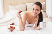 foto of bed breakfast  - Pretty brunette having breakfast in bed at home in the bedroom - JPG