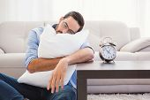 Exhausted man sleeping with head resting on pillow in the living room