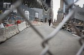 NEW YORK - SEPT 11, 2014: A New York City Policeman walks through the construction zone at the One World Trade Center building in Lower Manhattan, as seen through the safety fence.
