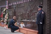NEW YORK - SEPT 11, 2014: A firefighter pays his respects at the Memorial Wall at FDNY Engine 10 Ladder 10 House on Liberty St . The firehouse is directly across from the WTC site.