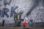 NEW YORK - SEPT 11, 2014: An unidentified man walks by a mural that says We Love New York featuring a firefighter spraying water from a hose on the anniversary of the 2001 terror attacks in Manhattan.