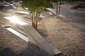 ARLINGTON, VA - SEPT 13, 2014: Sun reflects off a memorial unit at the Pentagon Memorial. Granite and stainless steel cantilevered benches have pools of water and names of victims of the 2001 attack.