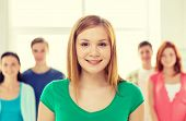 education and school concept - group of smiling students with teenage girl in front