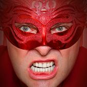 Close up portrait of angry man in red mask. Mental health concept.